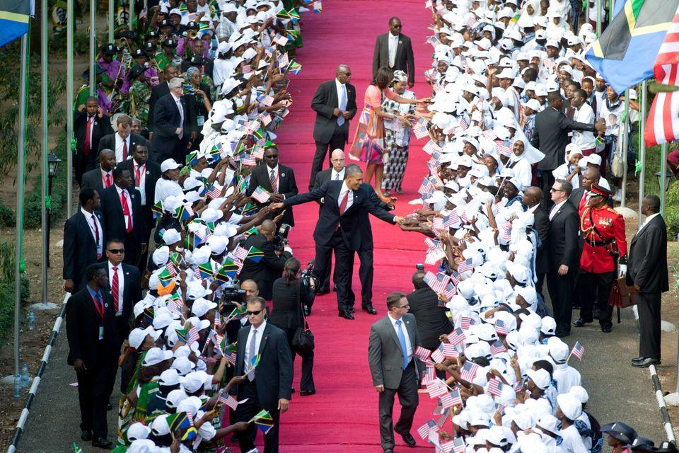 President Barack Obama and Tanzanian President Jakaya Kikwete walk in front of first lady Michelle Obama and Tanzanian first