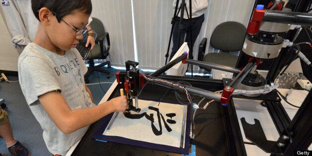 A boy writes a Chinese letter for 'study' with a calligraphy robot, which mimics the exact brush strokes of a master calligra