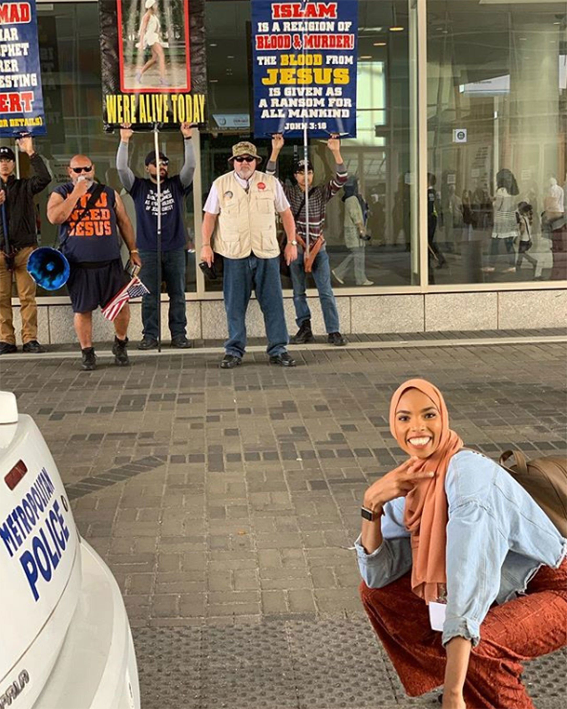 Muslim Woman Responds To Bigotry With A Smile In Photo With Protesters