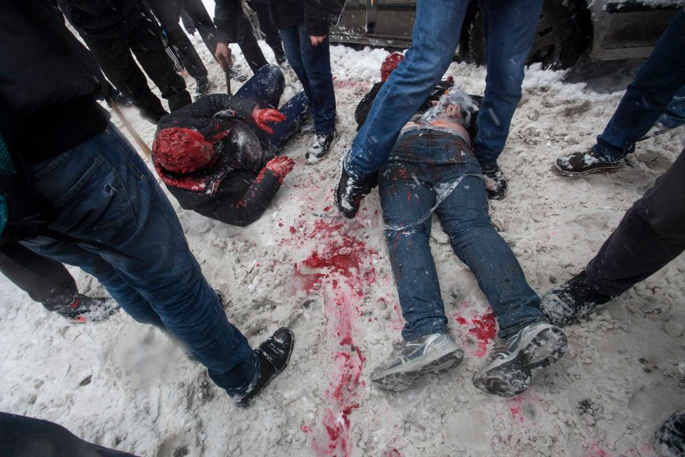 In this photo taken on Friday, March 15, 2013, members of a pro-Kremlin youth group douse with red paint two tied-up pushers