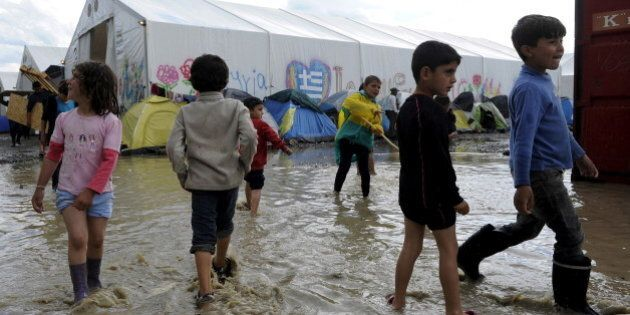 Children play in a puddle following heavy rainfall at a makeshift camp for migrants and refugees at the...