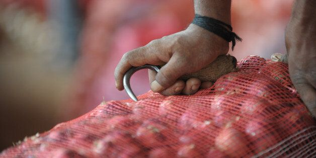 An Indian labourer prepares to carry onion bags towards waiting transport vehicles at a wholesale market yard in Hyderabad on