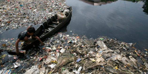 A boy collect plastics from a polluted river in Jakarta March 21, 2010. The Earth is literally covered...