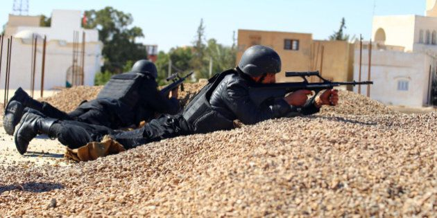 Tunisian police officers take positions as they search for attackers still at large in the outskirts...
