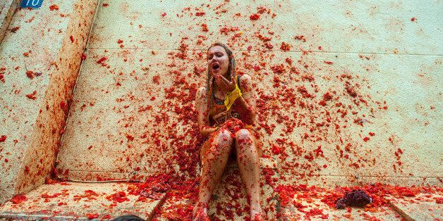 BUNOL, SPAIN - AUGUST 28:  Revellers celebrate covered by tomato pulp while participating the annual Tomatina festival on Aug