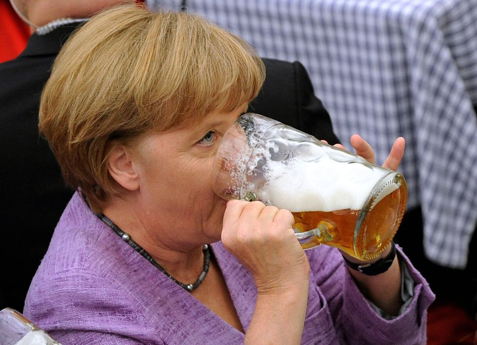 German Chancellor Angela Merkel drinks beer in a beer tent during a fair in Abensberg, southern Germany, Monday, Sept. 3, 201