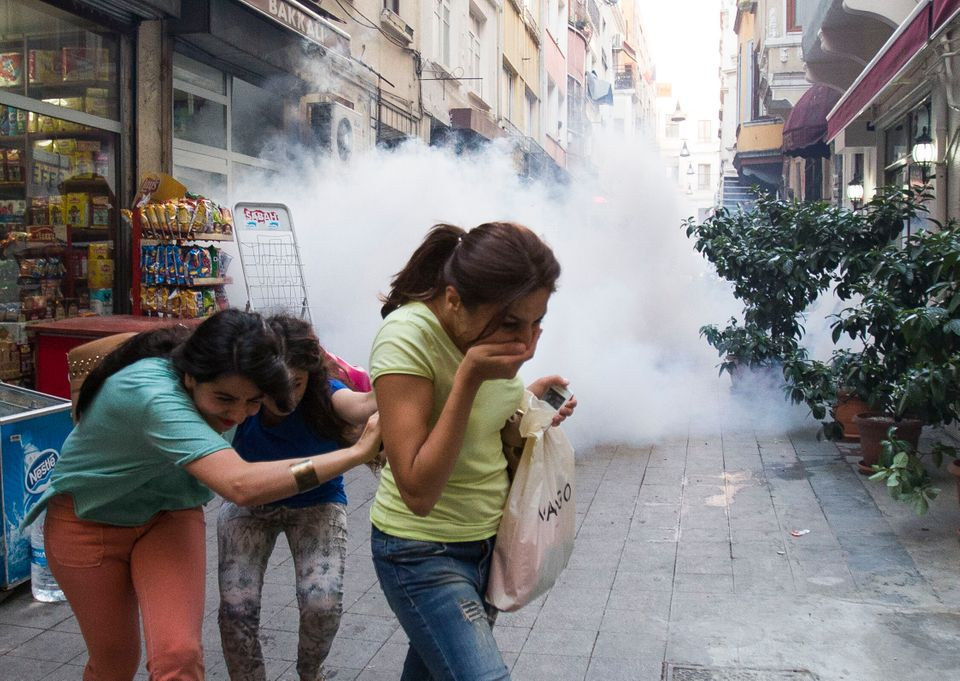 Three women take cover as they try to escape tear gas shot by police against protesters during clashes in Istanbul, Turkey, M