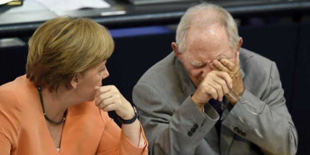 German Finance Minister Wolfgang Schaeuble (R) and German Chancellor Angela Merkel chat during a session...