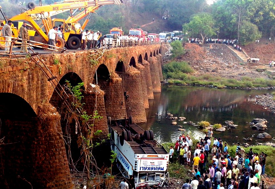 Rescuers and others gather at the site of a bus accident in Ratnagiri district, in the western Indian state of Maharashtra, T