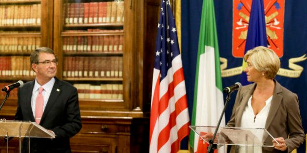 Italian Defense Minister Roberta Pinotti, right, and US Secretary of Defense Ashton Carter look at each...