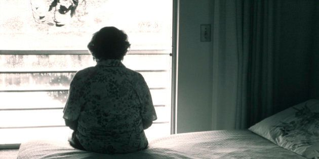 Elderly woman Sitting On Her Bed Looking Out