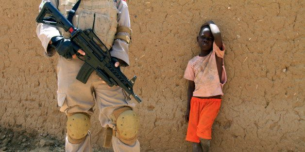 A young boy watches a United Nations peace keeper in the North Darfur state capital of El-Fasher, on June 17, 2013. The openi