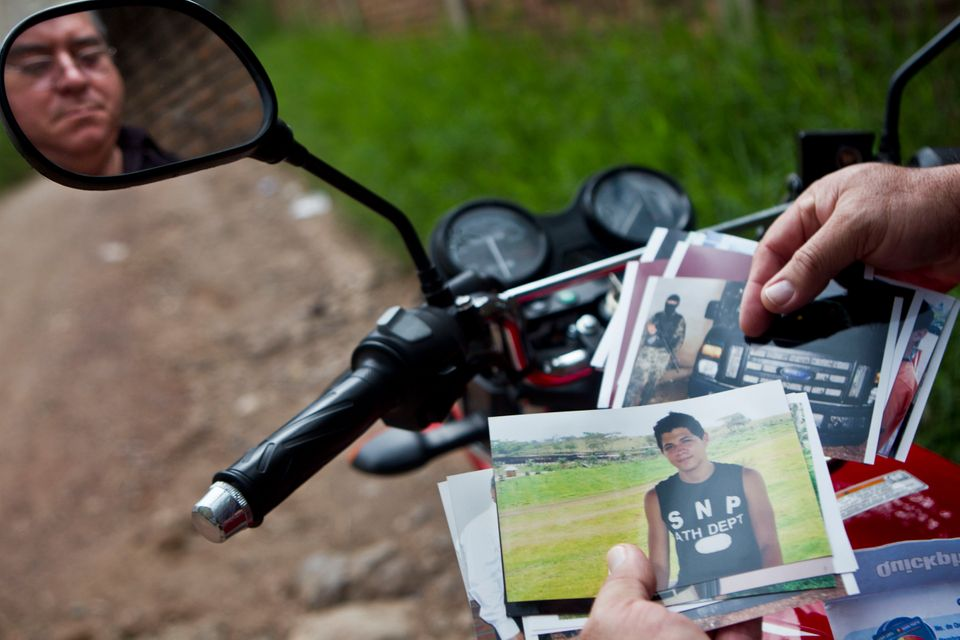 In this Oct 17, 2012 photo, Wilfredo Yanes, reflected on a mirror of his motorcycle, shows pictures of his late son Ebed Jaa