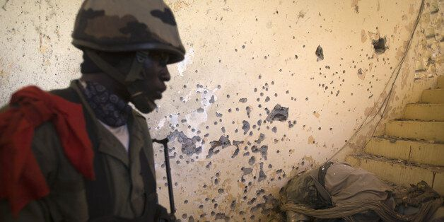A Malian soldier discovers the body of an Islamist soldier in the Court in central Gao on February 22, 2013. Five people, inc