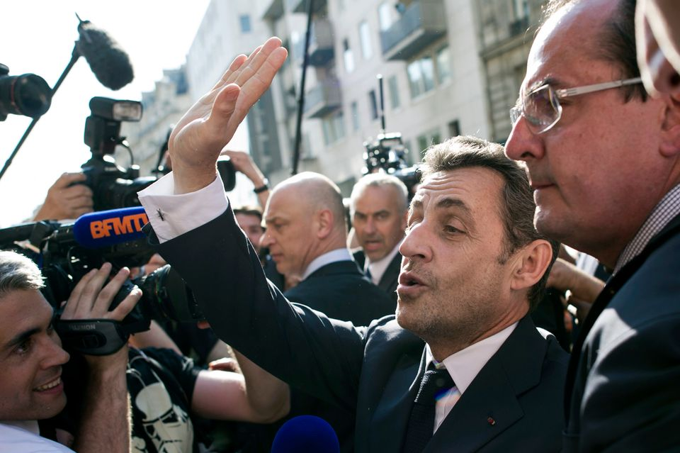 Former French President Nicolas Sarkozy waves as he leaves the UMP right-wing party headquarters on July 8, 2013 in Paris. (F