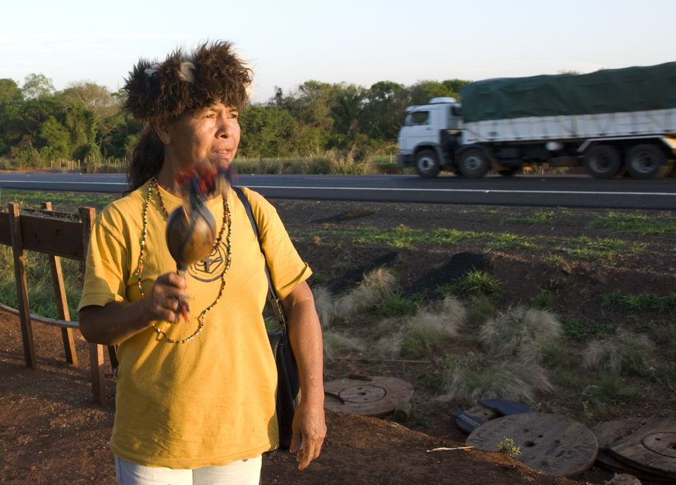 Damiana Cavanha stands by the side of a Brazilian road, a blue-feathered maraca made from a pumpkin gourd in one hand, and st