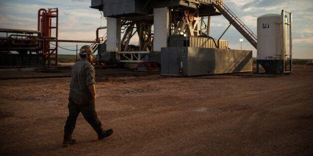 WATFORD CITY, ND - JULY 28:  Leslie Lindeman, a motor man for Raven Drilling, works on an oil rig drilling into the Bakken sh