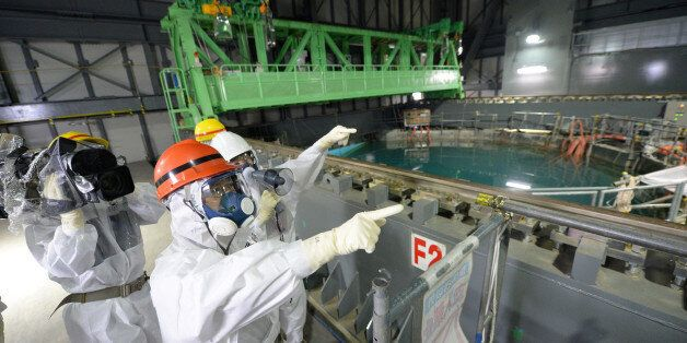 Fukushima Governor Yuhei sato (orange helmet) inspects the spent fuel pool in the unit 4 reactor building of Tokyo Electric P