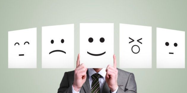 Business man holding up smiley face in front of