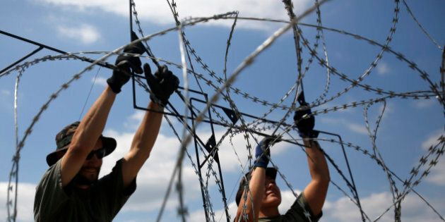 Hungarian soldiers place a barbed wire near Morahalom, Hungary, Thursday, July 16, 2015. A fence on Hungary's...