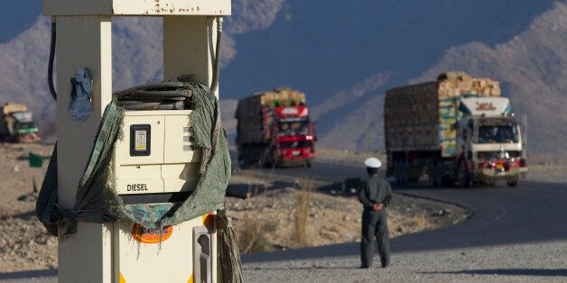 An Afghan policeman watches trucks driving on the highway 7, route between Pakistan and Afghanistan, next to a petrol station