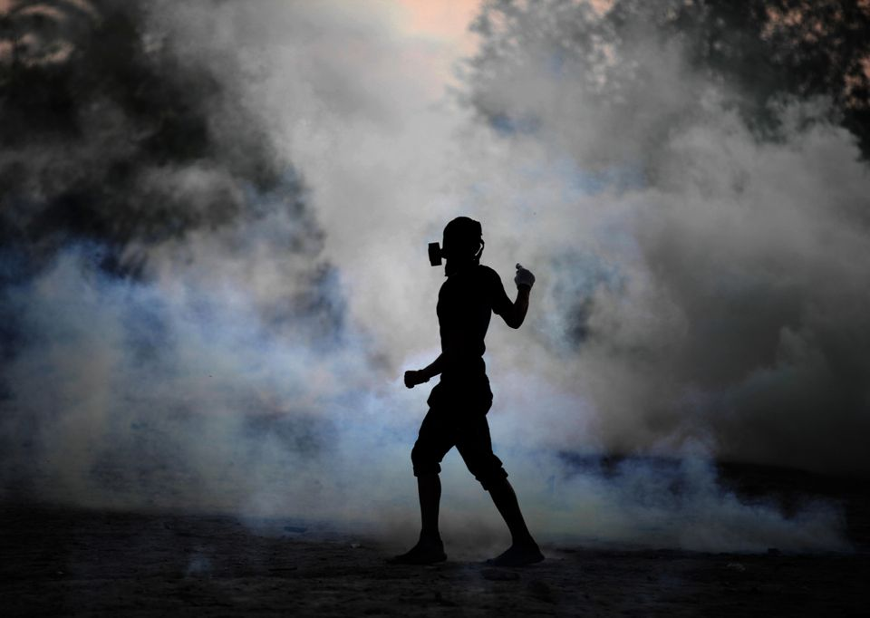 A Bahraini anti-government protester reacts to tear gas fired by riot police, unseen, in the village of Shakhura, Bahrain, Th