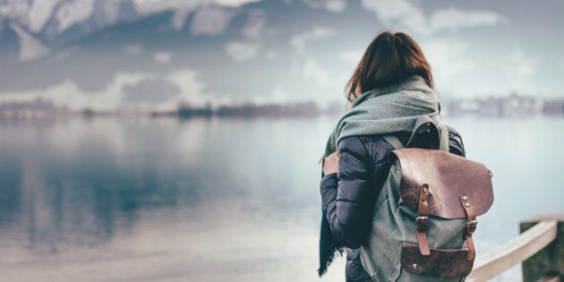 Hipster young girl with backpack enjoying landscape standing near the