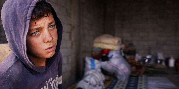 MAJDAL ANJAR, LEBANON - NOVEMBER 12: Bashar, an 11 year old Syrian refugee, stands near an empty garage he shares with member
