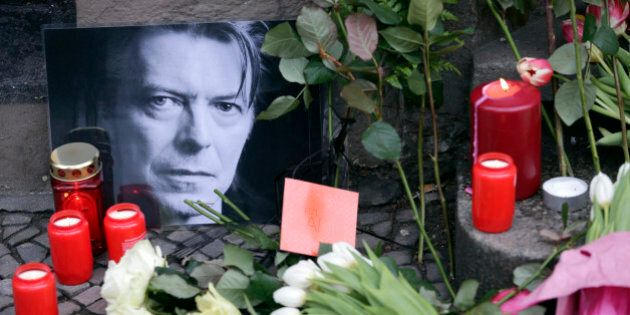 Flowers and a portrait are placed in front of the apartment building where David Bowie once lived in...