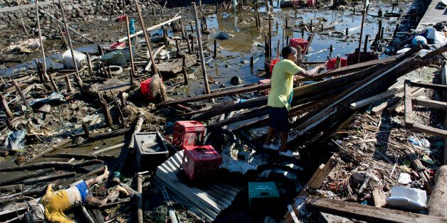 A victim lies among debris as a man (C) efforts to rebuild his house on stilts that had been swept away by the typhoon in a T
