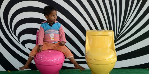 A young Indian child plays on toilets during a 'Toilets are Beautiful' campaign on the occasion of World Toilet Day in New De