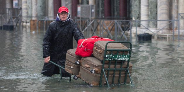 VENICE, ITALY - NOVEMBER 19: A baggage porter  struggles under torrential rain and wind during High Water on November 19, 201