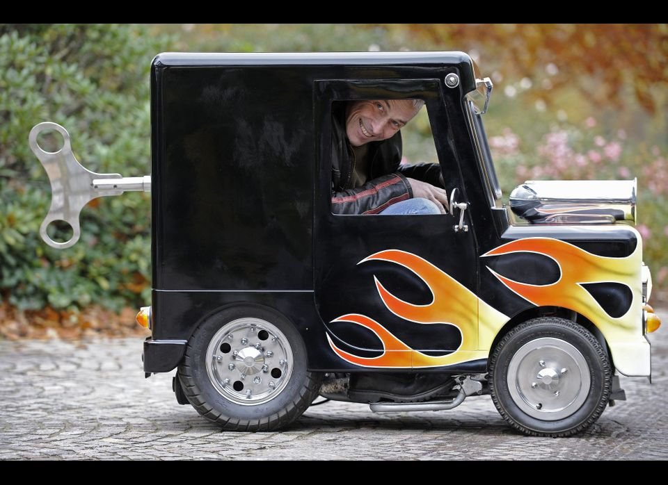 """British constructor Perry Watkins sits in his """"Wind Up"""" mini car, listed as the world's smallest car with a license to drive"""