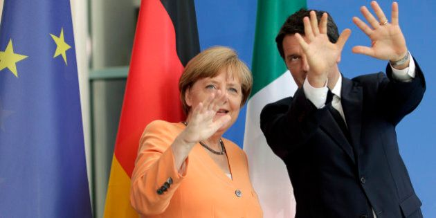 German Chancellor Angela Merkel, left, and the Prime Minster of Italy, Matteo Renzi, right, gesture after...