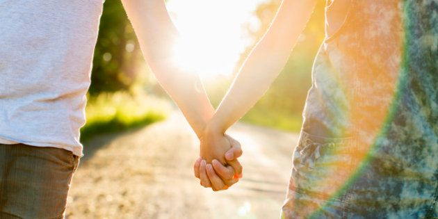 Midsection of couple holding hands on dirt road against bright