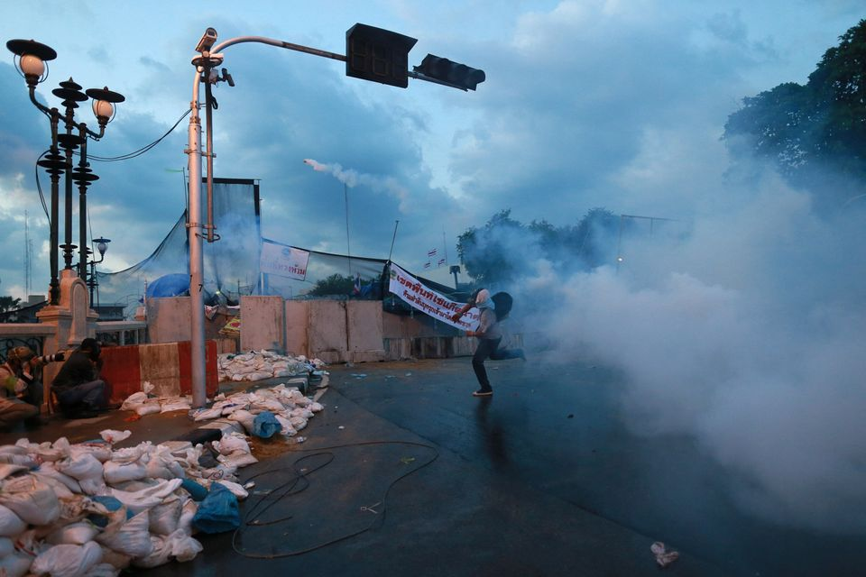 An anti-government protester throws back a tear gas canister fired by riot police in Bangkok, Sunday, Dec. 1, 2013. (AP Photo