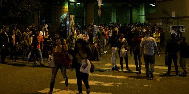 People stand outside a subway station during a general blackout in Caracas on December 2, 2013. AFP PHOTO/JUAN BARRETO