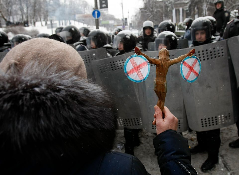 A woman holds a statue of Jesus in front police officers as they block a street after clashes in central Kiev, Ukraine, Wedne