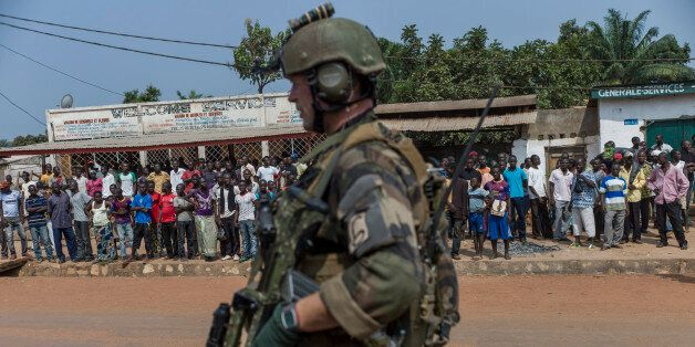 A French soldier  stands guard at a checkpoint in Combattant neighborhood near Bangui's airport, on December 9, 2013. French