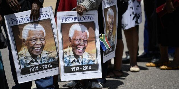 People hold portraits of Nelson Mandela as South Africans stand in line to pay their respect to South African former presiden