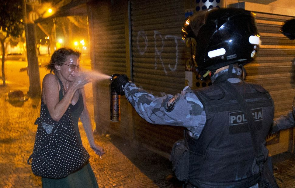 A military police pepper sprays a protester during a demonstration in Rio de Janeiro, Brazil, Monday, June 17, 2013. (Victor