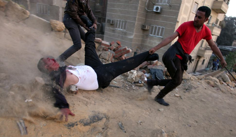 Egyptian protesters drag a wounded Muslim Brotherhood supporter during clashes between supporters and opponents of Egypt's po