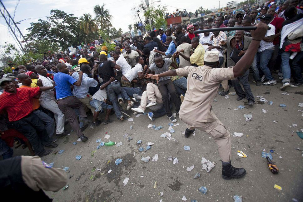 A police officer uses his baton to beat back supporters of Haiti's former President Jean-Bertrand Aristide who gathered outsi