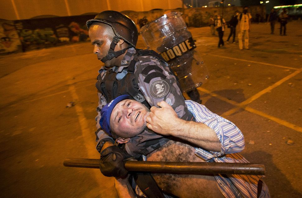 Military police detain a man during an anti-government protest in Rio de Janeiro, Brazil, Thursday, June 20, 2013.  (Victor R