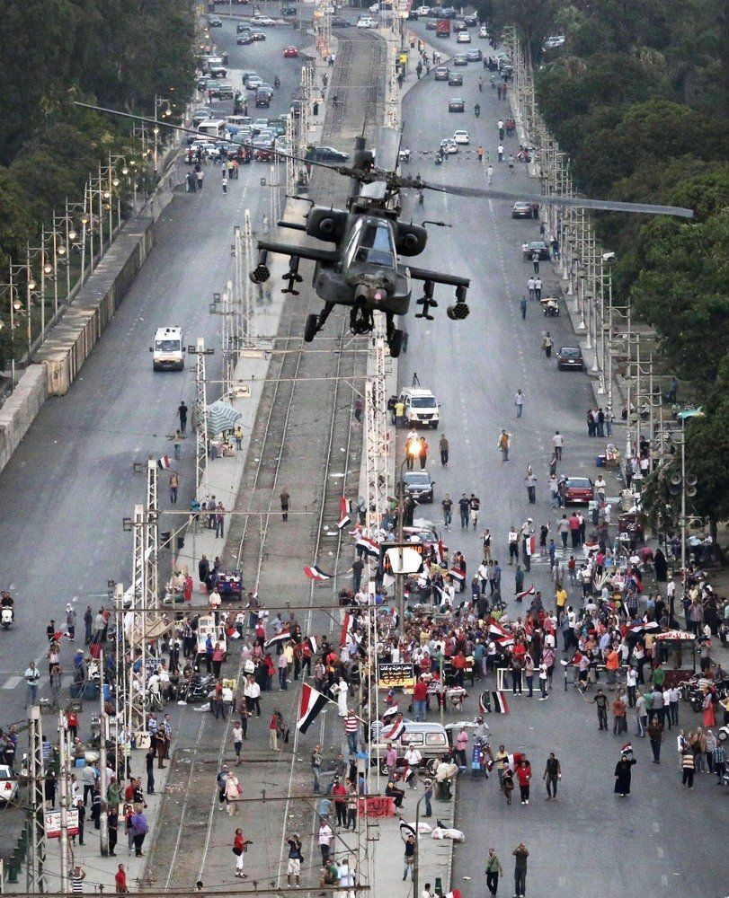 A military attack helicopter flies over a street near the presidential palace, in Cairo, Egypt, Friday, July 5, 2013 days aft