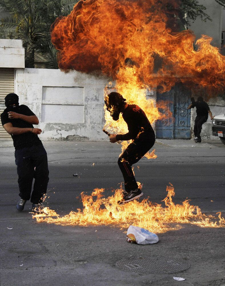 A Bahraini anti-government protester is engulfed in flames when a shot fired by riot police hit the petrol bomb in his hand d