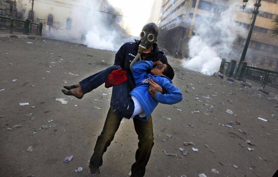 An Egyptian protester evacuates an injured boy during clashes near Tahrir Square, Cairo, Egypt, Friday, Jan. 25, 2013.  (Khal