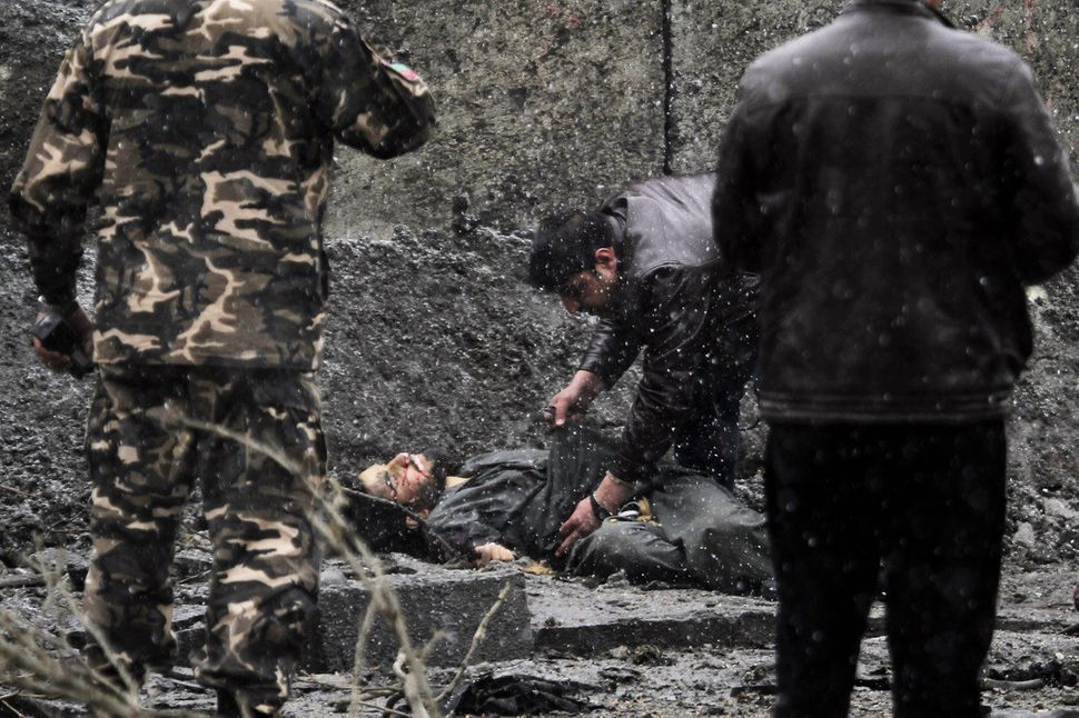 Afghan security and intelligence check a dead body at the scene after an attack by militants in Kabul, Afghanistan, Wednesday