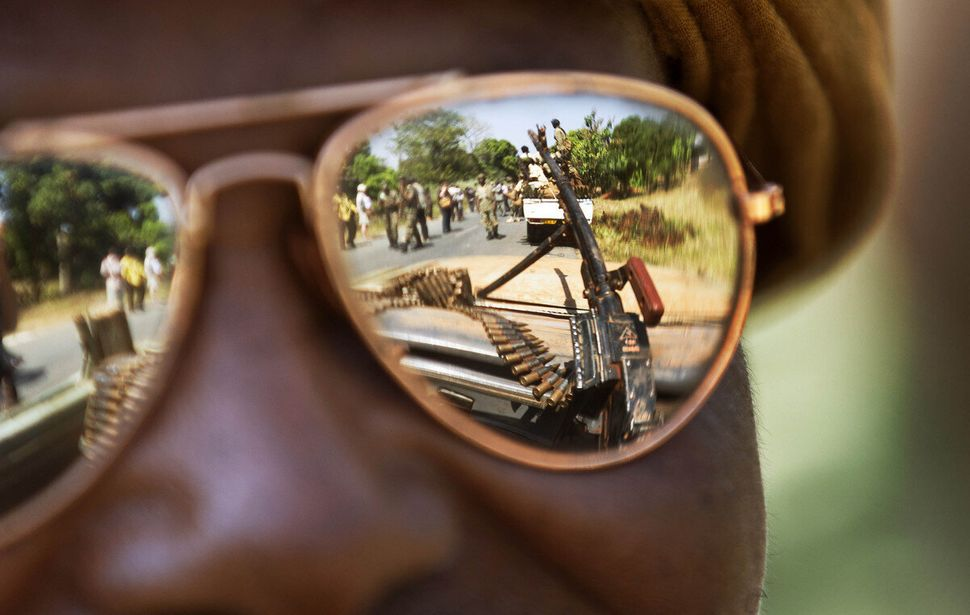A Chadian soldier wearing reflective sunglasses observes the convoy ahead of him, as Chadian soldiers who are fighting in sup