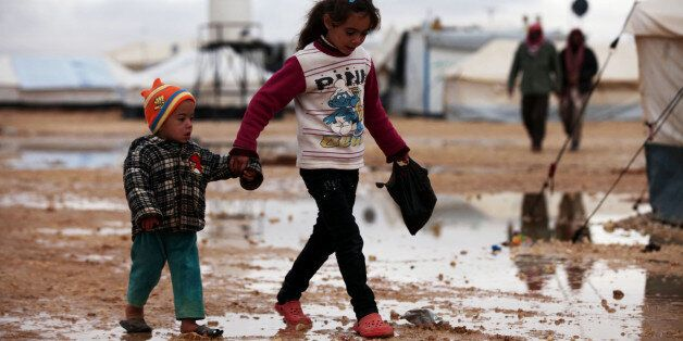 ZAATARI, JORDAN - DECEMBER 12: Syrian refugee children suffering from the heavy weather conditions walk on the mudy field aro